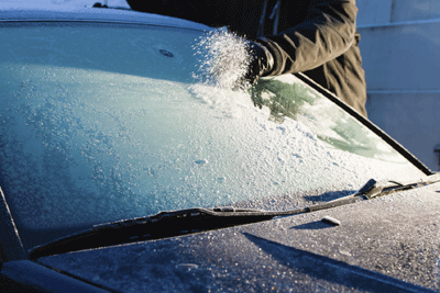 Image of someone scraping ice off a car windscreen