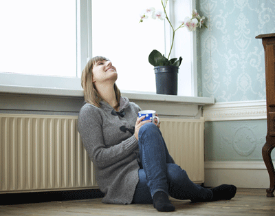 Happy woman next to central heating
