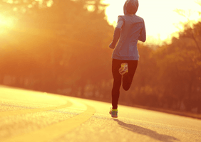 Image of a woman running at sunset