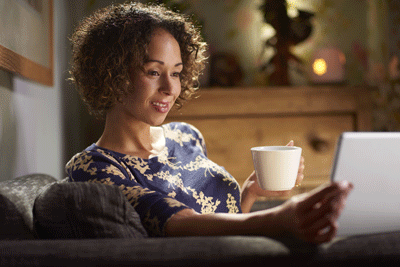 Image of woman looking at tablet with cup of tea