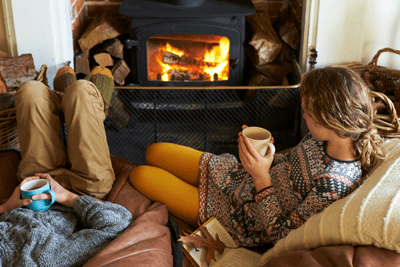 Image of a couple sitting by a fireplace