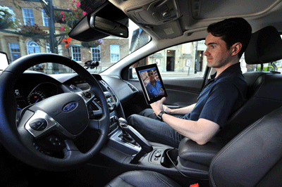 Image of a bloke in a car with a tablet