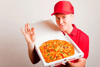 Image of a man giving an affirmative gesture whilst holding a pizza