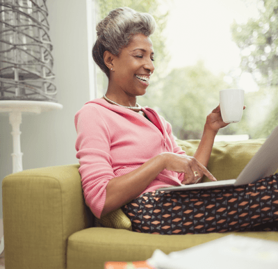Image of a woman drinking tea and smiling at laptop