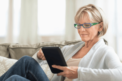 Image of a woman reclining on a sofa with tablet
