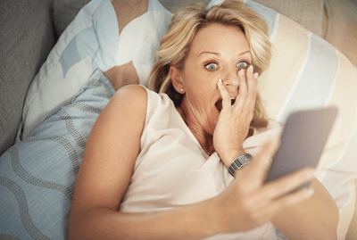 Image of a woman looking shocked at her phone