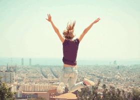 Woman jumping for joy above city