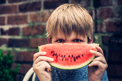 A boy holding watermelon