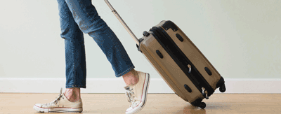 Woman confidently strolling with hand luggage