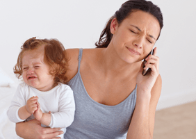 An unhappy woman on the phone with the baby