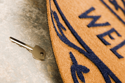 Image of key under welcome mat