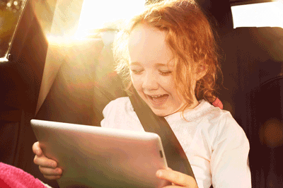Image of a delighted child looking at an ipad