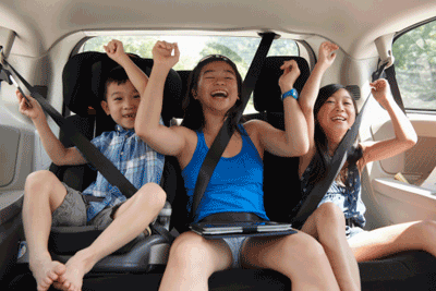 Image of some delighted children in the back of a car