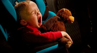 A child sleeping in a car