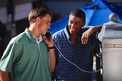 Image of boys using payphone