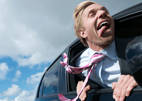 Image of businessman hanging out of window of car