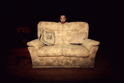 Image of man hiding behind sofa