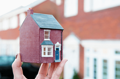 Hand holding a model house