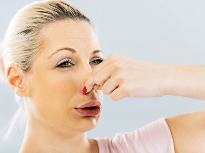 A woman holding her nose