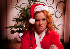 A disgruntled lady in front of  a Christmas tree, wearing festive attire