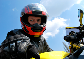 Man in helmet and leathers points at camera