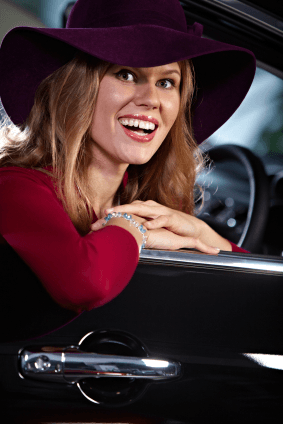 Cheerful young female driver wearing magnificent hat