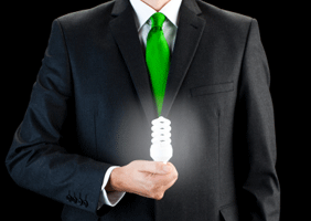Man in a suit with a green tie (face out of shot) presents an energy-saving lightbulb, as if to symbollically offer a bright idea.