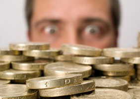 A gimlet eyed man, just out of focus, looks longingly at a big load of pound coins in the foreground