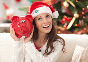 An attractive young woman in a Christmas hat, holding a red piggy bank with a joyful expression on his face.