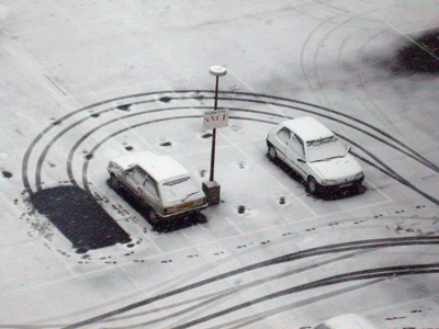 Cars in snowy car park with tyre marks