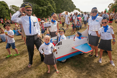 Image of kids and parents larking around in fancy dress at a festival