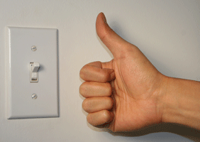 Image of an affirmative 'thumbs up' gesture next to a light switch