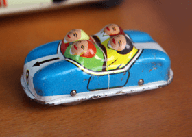 A picture of an old toy car containing four passengers.