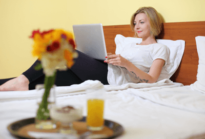 Woman on a bed with laptop open