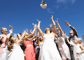 A picture of a bride throwing her wedding bouquet in the air