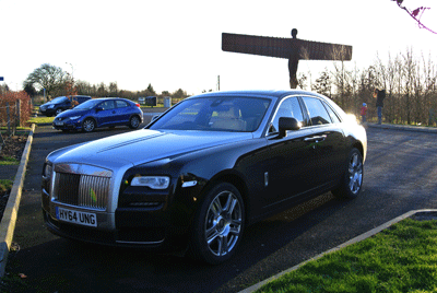 Image of the Rolls Royce Ghost with the Angel of the North behind it