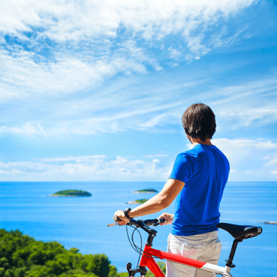 Man standing with bike looking out to sea in Croatia