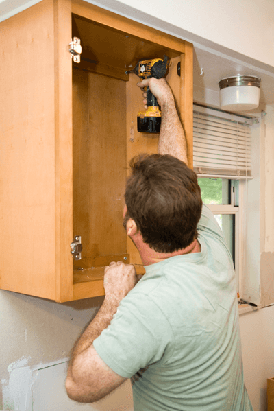 A picture of a man drilling a cupboard