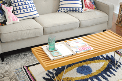 A photo of a sofa with coffee table and rug