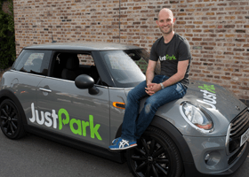 A photo of Alex Stephany from JustPark sitting on a Mini Cooper