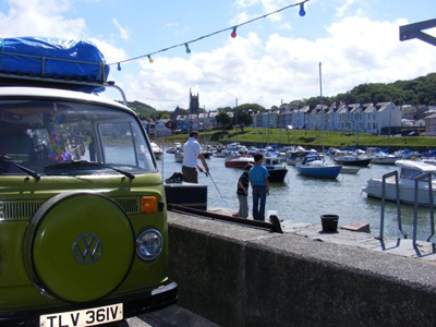 Children fishing by a Volkswagon campervan