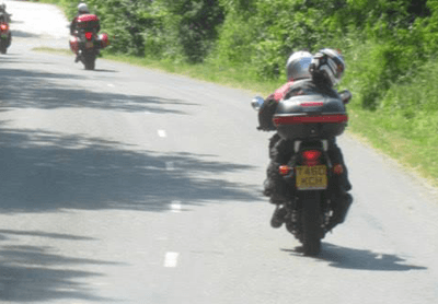 A bike with a pillion passenger
