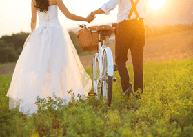 A newly-married couple walking through a field with a push bike
