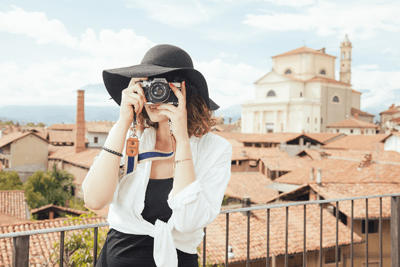 Image of a woman taking a picture on a balcony