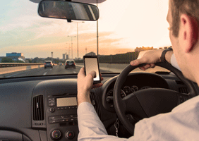Image of a man tinkering with a phone whilst driving