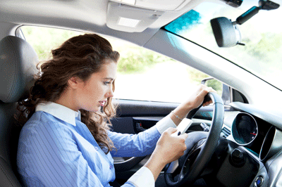 Image of someone looking at a mobile phone whilst driving