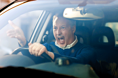 Image of a visibly irate man driving a car