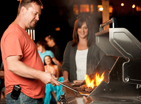 A man stands in front of his BBQ as a woman looks on