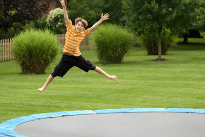 A small boy jumping on a trampoline