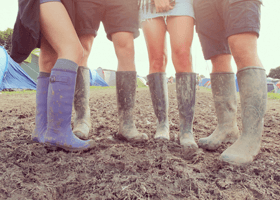 Four people at a festival wearing wellies